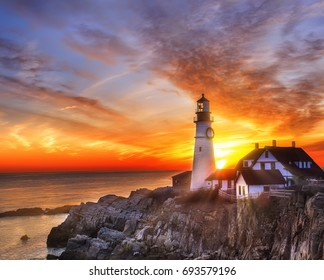 Lighthouse on the beach at dawn. A beautiful coastline covered with stones, the sun's rays illuminating everything around in the early morning. USA. Portland. Maine.