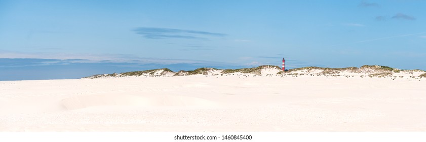 Lighthouse on the beach of an island  with fine white sand, beach sand, dunes and grasses, blue sky on the North Sea, Amrum