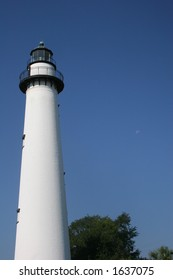 Lighthouse on coast with sky and moon in background