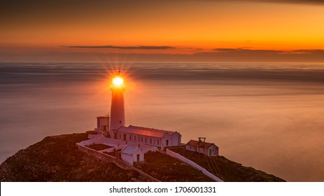 Lighthouse on coastal island with horizon and beautiful sunset at South Stack in Holyhead, North Wales. South Stack lighthouse at sunset overlooking the Irish Sea Isle of Anglesey