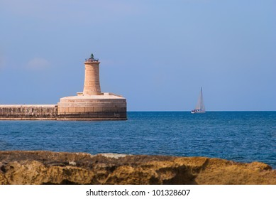 The lighthouse on the end of the Grand Harbor Breakwater seen from the opposite shore on a clear bright day.
