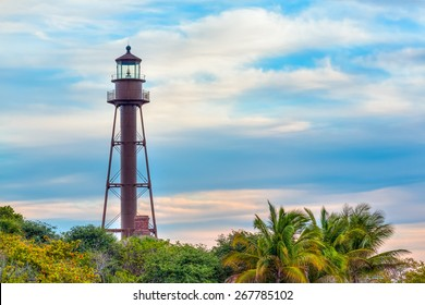 The lighthouse on Florida's Sanibel Island rises above tropical trees against a cloudy blue sky.