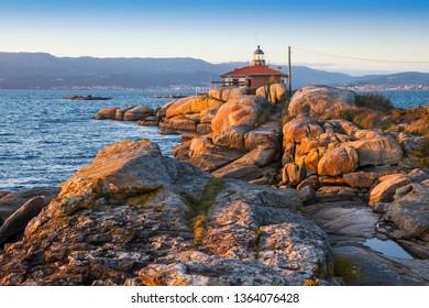 Lighthouse on the granite rocks of Punta Cabalo cape in Arousa Island