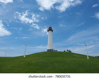 Lighthouse on a green hill under the blue sky