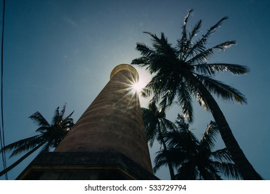 A lighthouse on an island close to palm trees with a clear blue sky in the background from underneath