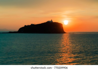 lighthouse on the island Skryplev in the light of the sunrise from the Harbor Parking of the city of Vladivostok