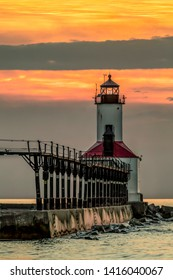 The lighthouse on Lake Michigan at Michigan City, Indiana is backed by a cloudy and colorful sunset sky.