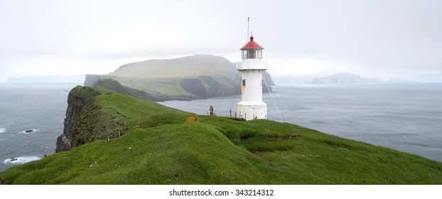 Lighthouse on Mykines Holmur with rocks, green, grass and beautiful landscape of the Faroe Islands
