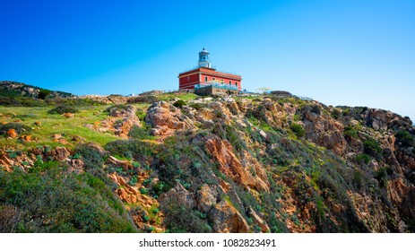 Lighthouse on the promontory with blue sky.  Capo Spartivento Lighthouse in the coast of Teulada, Sardinia.