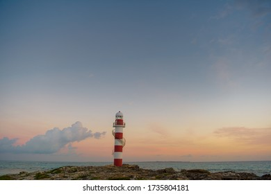 Lighthouse on a rocky shore in Cancun. Clear sky and blue sea. Mexico.