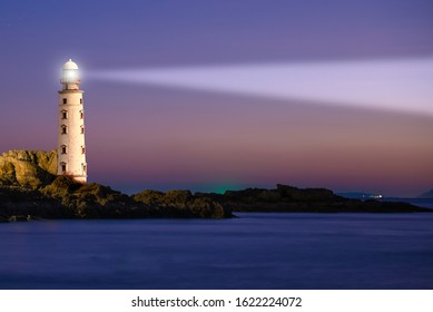 Lighthouse on sea sunset with light beacon at night landscape