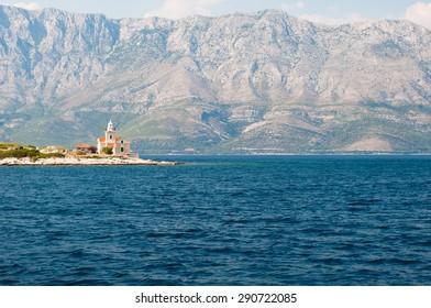 Lighthouse on south end of island Hvar in Adriatic sea with mountain Biokovo in background. Sucuraj, Croatia