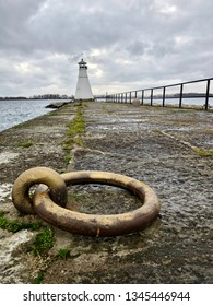 Lighthouse on a stone pier with railing on the side and iron ring in front.