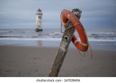 The �Point of Ayr� lighthouse on Talacre Beach  Wales with footpath sign in the foreground and red life ring.