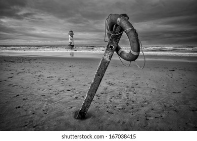 The �Point of Ayr� lighthouse on Talacre Beach  Wales with footpath sign and life ring in black and white.