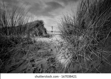 The �Point of Ayr� lighthouse on Talacre Beach  Wales with evening light through the dunes in black and white