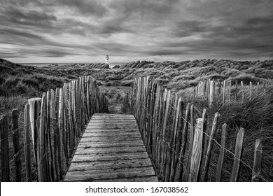 The �Point of Ayr� lighthouse on Talacre Beach  Wales looking through the dunes over the walk way in black and white.