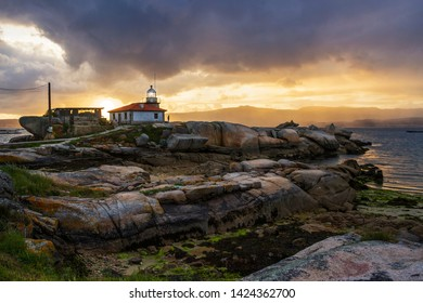 Lighthouse over the coastal rocks of Cabalo Point in Arousa Island at stormy sunset