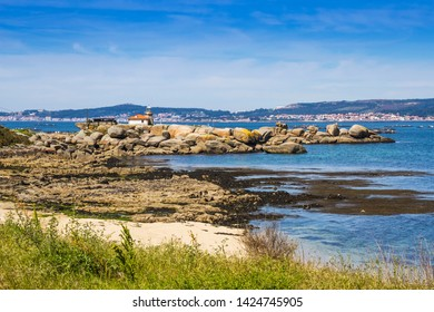 Lighthouse over the coastal rocks of Cabalo Point in Arousa Island