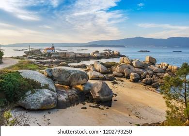 Lighthouse over coastal rocks in Punta Cabalo cape, Arousa Island, Galicia, Spain