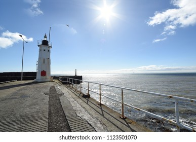 Lighthouse at the pier in the harbour of Anstruther, a bright sunny day with white summer clouds, near St. Andrews in The Kingdom of Fife, Scotland.