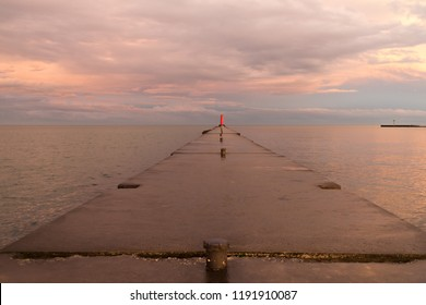 A lighthouse pier on Lake Michigan at sunset with pink clouds reflected in the water.  Sheboygan, Wisconsin, USA.