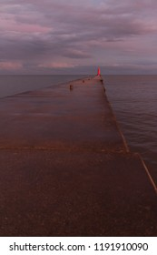 A lighthouse pier on Lake Michigan at dusk with pink clouds reflected in the water.  Sheboygan, Wisconsin, USA.