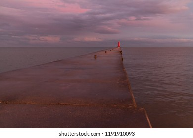 A lighthouse pier on Lake Michigan at dusk with purple clouds reflected in the water.  Sheboygan, Wisconsin, USA.