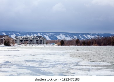 Lighthouse point condominiums look over Blue Mountain Ski hills from a distance, with the frozen Georgian Bay water beside it in the winter