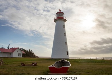 Lighthouse at Point Prim with wooden rowboat on Prince Edward Island, Canada against cloudy blue skies on sunny day.