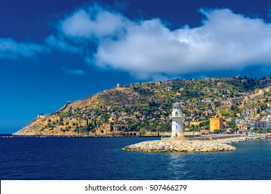 Lighthouse in the port of Alanya with view on beach and mountain in Turkey