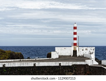 Lighthouse at the port of the Azores island Flores in stormy weather, overlooking the sea.