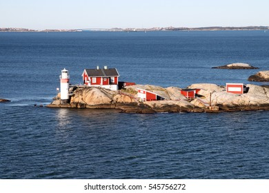 Lighthouse and red buildings on small rocky island in the archipelago on the North Sea at Gothenburg, Sweden in Scandinavia