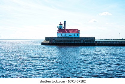 Lighthouse with a red roof at the end of a pier at Duluth harbor in  Minnesota, while wispy white morning clouds drift above it.