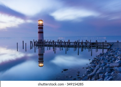 A lighthouse reflected in a lake during colorful sunset. Stony shore and wooden pier complement the amazing scene.