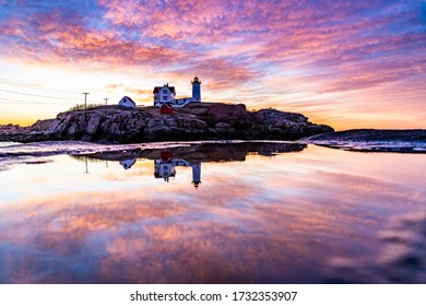 Lighthouse reflecting in water during sunrise.