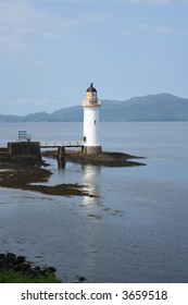 Lighthouse with reflection on isle of Mull Scotland