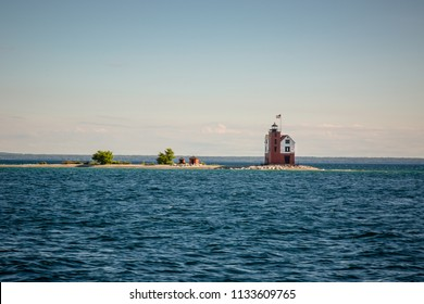 A lighthouse resembling a small house with a white and brick colored exterior and topped with a light and flag, sits on a tiny, rocky island in Lake Huron, near the shore of Mackinac Island, Michigan.
