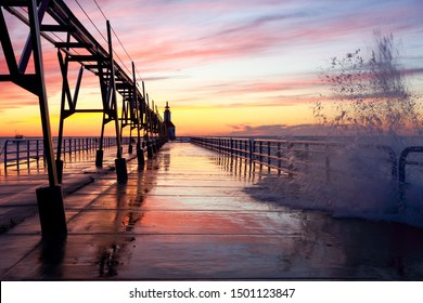 Lighthouse in Saint Joseph Michigan on a wavy summer evening at sunset, focus on railing and pier, motion blur on water