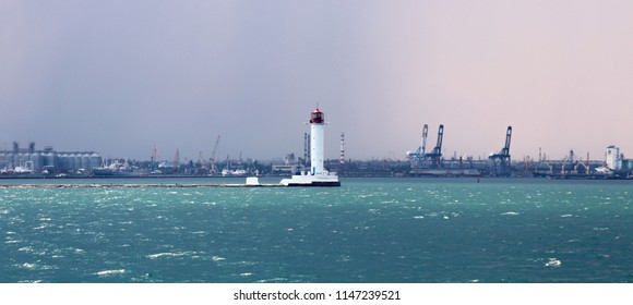 Lighthouse in the sea against the backdrop of a cargo port. Summer seascape with a white lighthouse with red top. Black Sea. Sea Port of Odessa.