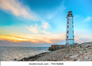 Lighthouse at sea coast with sunset sky