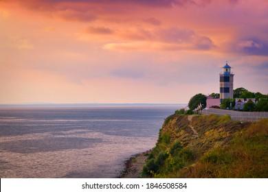 Lighthouse sea rock sunset landscape. Sunset lighthouse scene. Beautiful sunset view in Anapa.