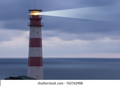 Lighthouse searchlight beam through marine air