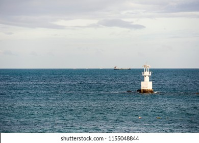Lighthouse and ship in the sea.