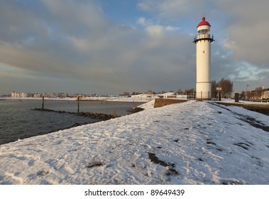 Lighthouse and snow covered jetty