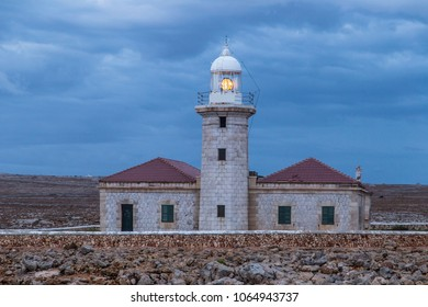 Lighthouse in spain under a cloudy skay, surrounded by rocks