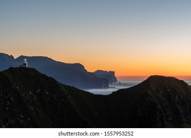 A lighthouse stands tall on a silhouetted mountain peak overlooking a glorious warm sunset and blue ocean at Kalsoy in the Faroe Islands. Taken September 2019.