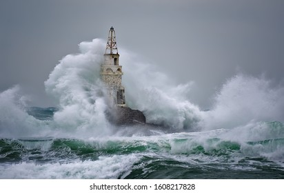 Lighthouse In Stormy Landscape. Storm waves over the Lighthouse -Ahtopol, Black Sea, Bulgaria.