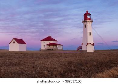 The Anse-à-la-Cabane lighthouse at sunset on Havre Aubert Island, Quebec, Canada