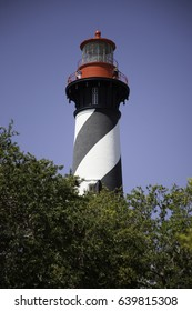 Lighthouse in the sunshine, over the tree tops